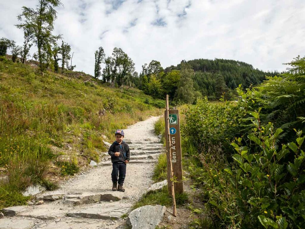 image of boy at Ben A'an trailhead next to the trailhead marker