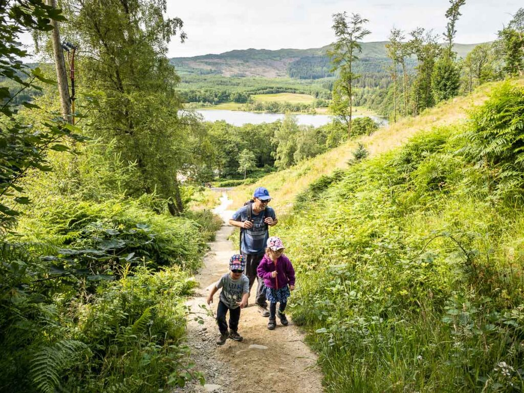 image of father with two kids on hiking trail up to Ben A'an summit in Loch Lomond and the Trossachs National Park Scotland