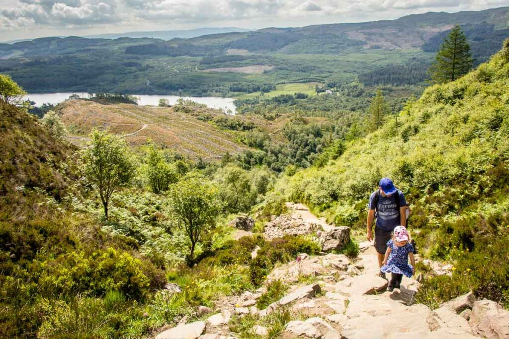 image of father and girl hiking up rock steps with green hills, trees and a lake in the distance on Ben A'an hike with kids in Trossachs National Park Scotland