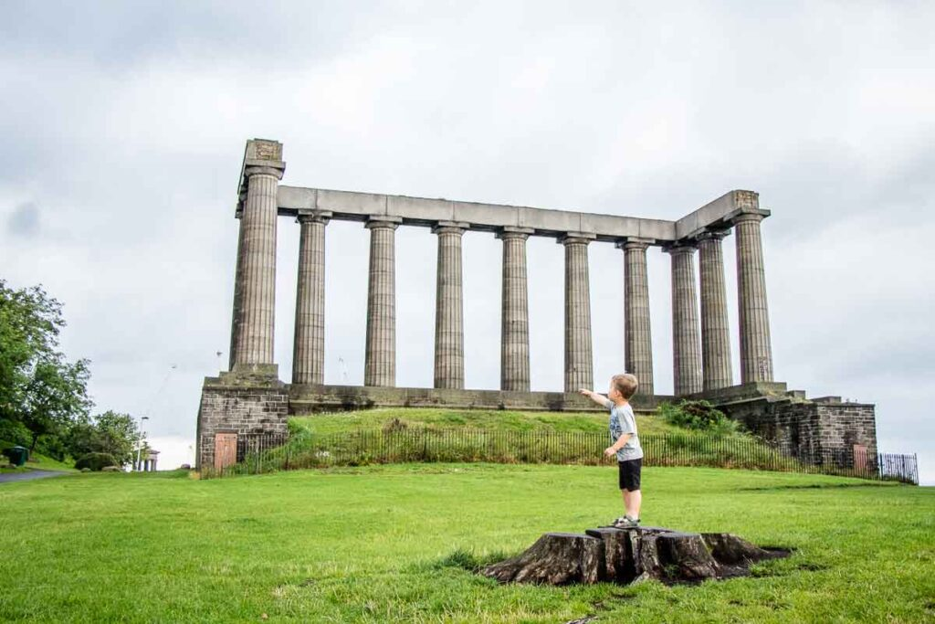 image of boy in front of National Monument of Scotland in Edinburgh
