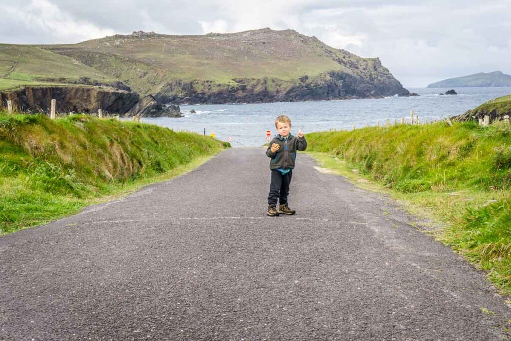 image of boy on road with ocean and hills in the background on Dingle Peninsula walk