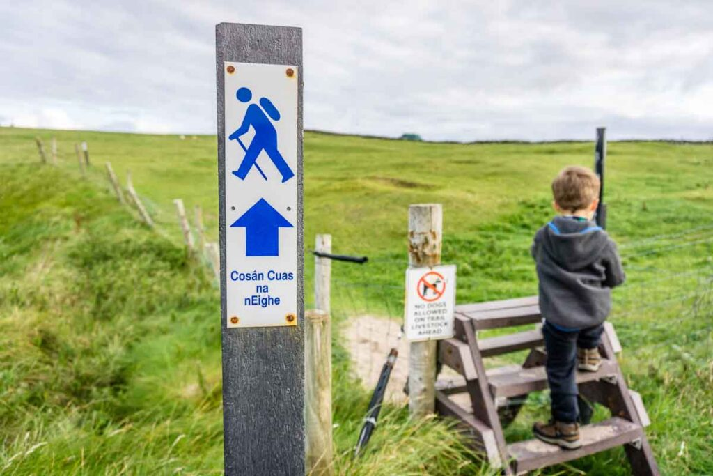 Image of Clogher Beach loop trail marker with boy in background climbing up ladder over a fence on Dingle Peninsula