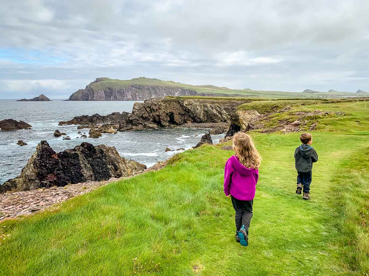 image of boy and girl walking on grassy path with beach and cliffs in the distance