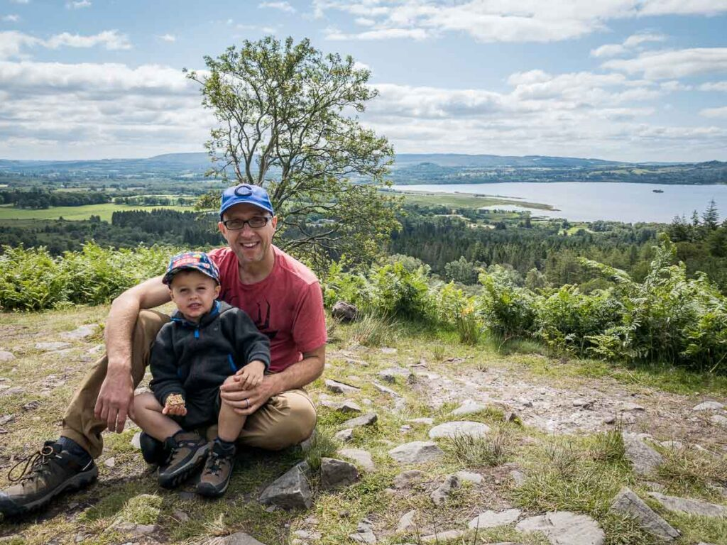 image of father sitting with boy on his lap eating a sandwhich with Loch Lomond and trees in the background in Loch Lomond Scotland