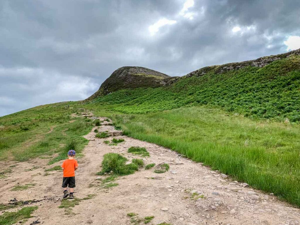 image of boy on hiking trail with Conic Hill summit in front of him
