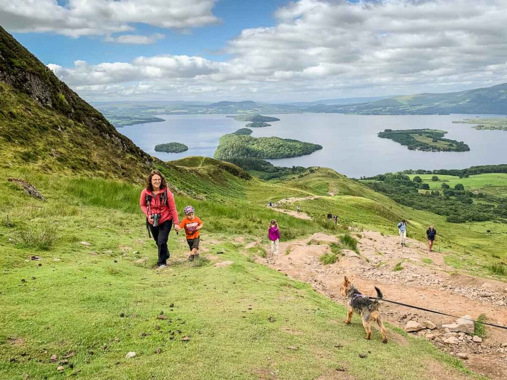 image of mother and boy on conic hill walk looking at a dog on leash