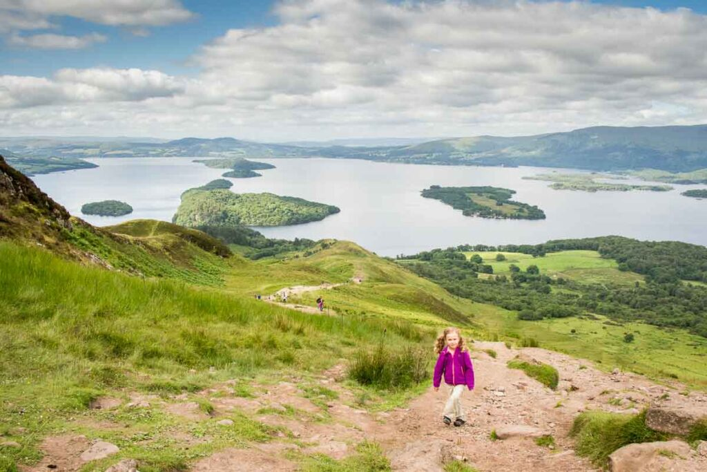 Image of girl in purple hoodie hiking up Conic Hill walk with Loch Lomond behind her