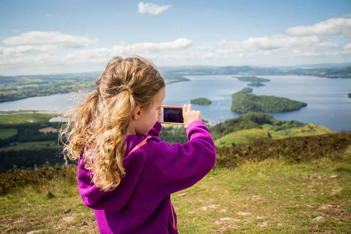 image of girl taking picture with a phone at the top of conic hill which is one of the best Loch Lomond walks to do with kids