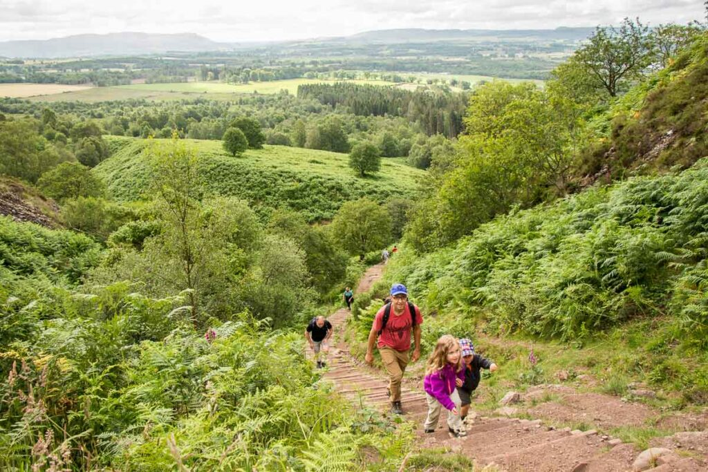 image of father and two kids on Conic Hill hiking trail with trees and green hills in the background in Loch Lomond National Park Scotland