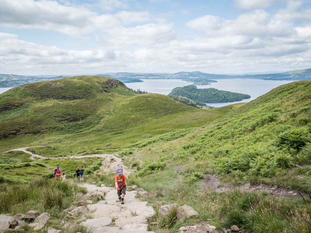 image of boy hiking up trail on Conic hill with Loch Lomond in the distance