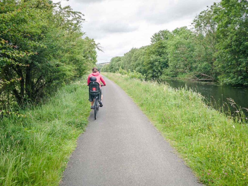 image of woman riding bike with toddler in bike seat on Forth & Clyde Canal Towpath near Glasgow Scotland