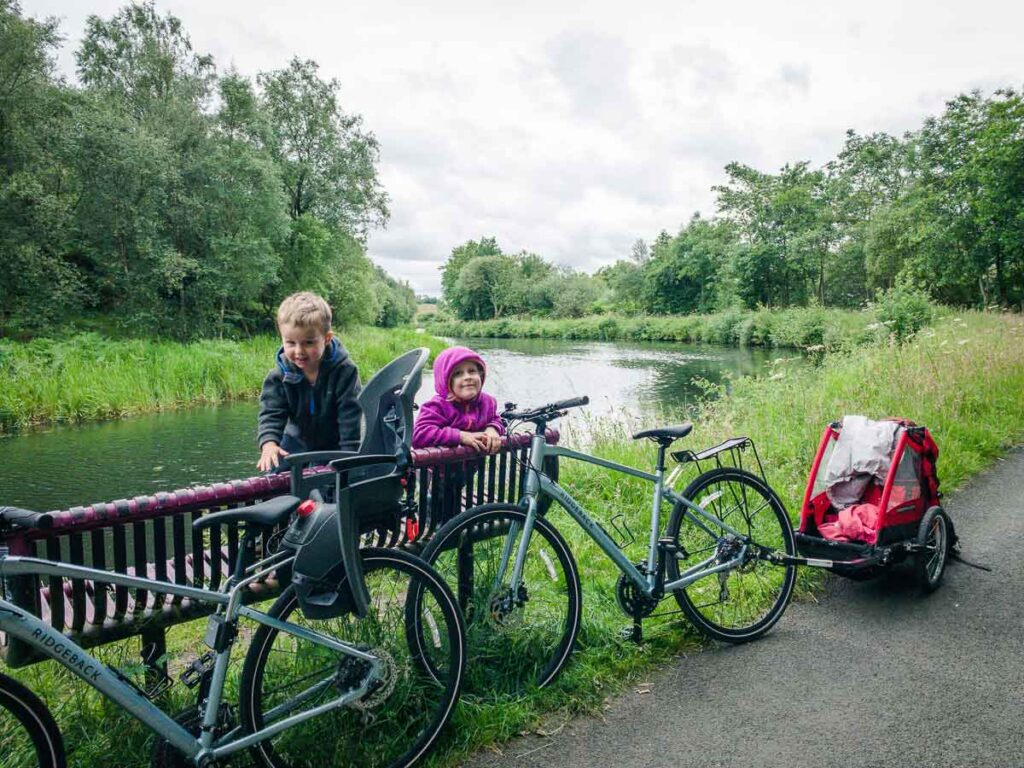 image of kids on a bench with bikes parked nearby along Forth and Clyde Canal Towpath Glasgow Scotland
