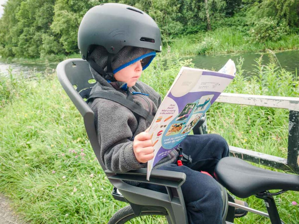 image of boy in bike seat reading a magazine and wearing a helmet