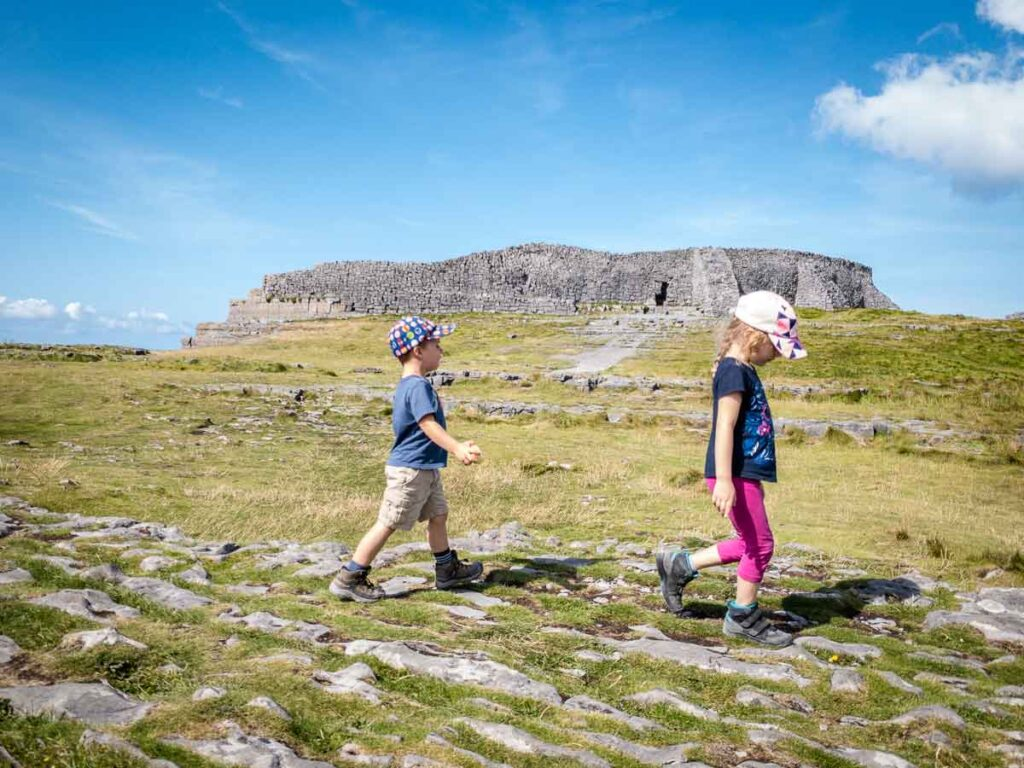 image of two kids walking in front of Dun Aonghasa, which is one of the best things to see on Inishmore with kids