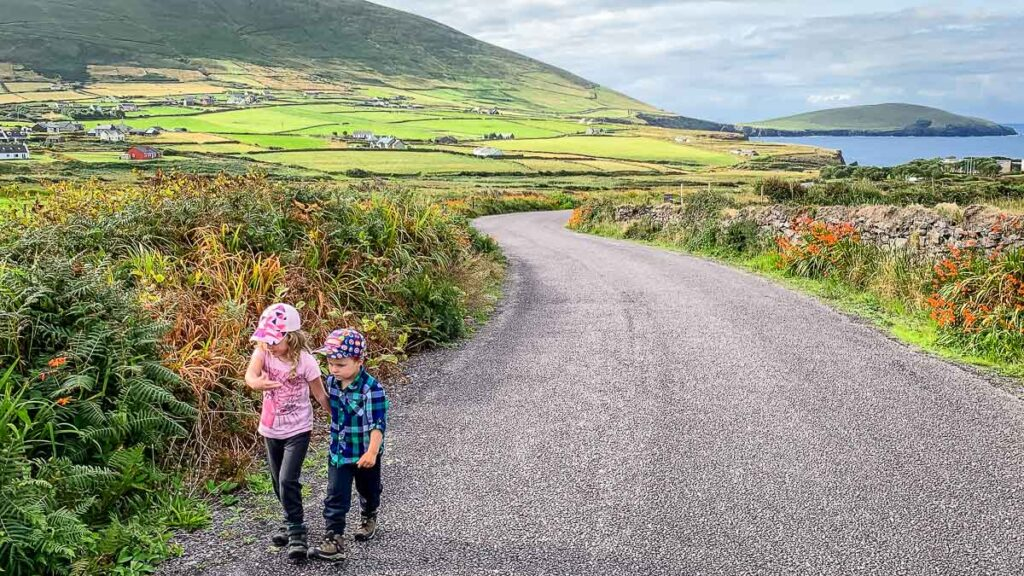 image of two kids walking along a road with rolling hills in the background on Dingle Peninsula in Ireland