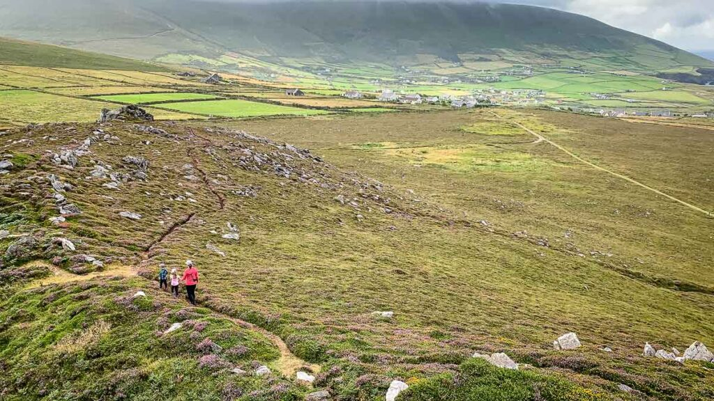 image of mother and two kids hiking in the distance on Dingle Peninsula