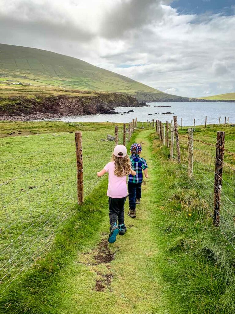 image of two kids running along a path with a fence on both sides and towards the ocean