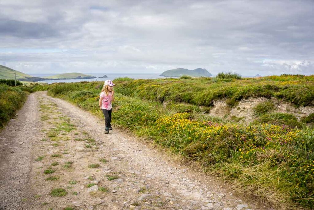 image of girl in pink shirt walking along gravel road on Dingle Peninsula in Ireland