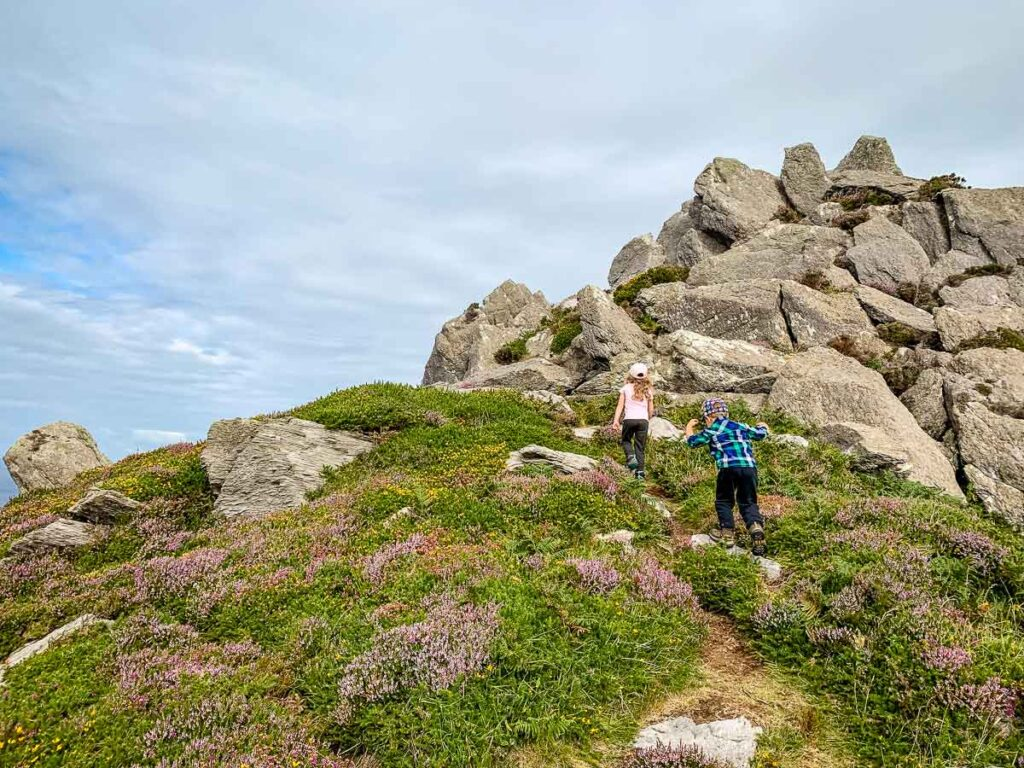 image of two kids hiking up to a large rock pile on Dingle Peninsula