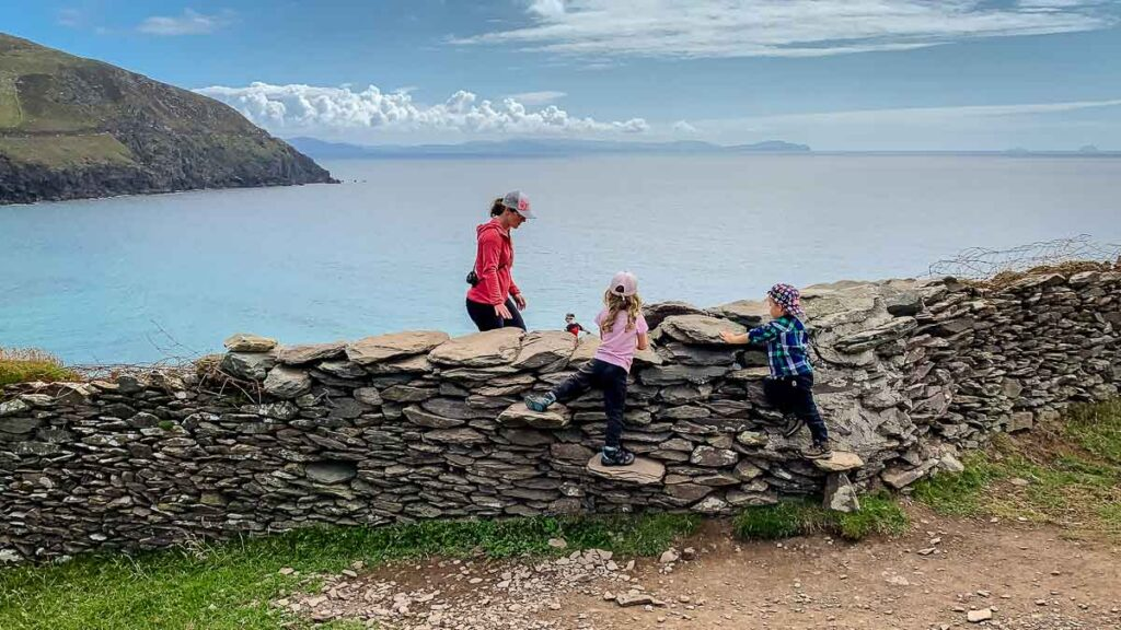 image of mother and two kids climbing over a rock wall on Dunmore Head Loop walk on Dingle Peninsula