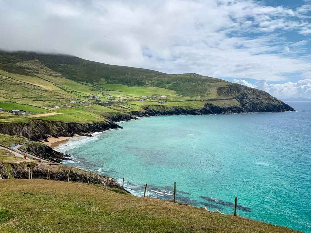 View of turquoise colored ocean and green hills from Dunmore Head Loop hike on Dingle Peninsula