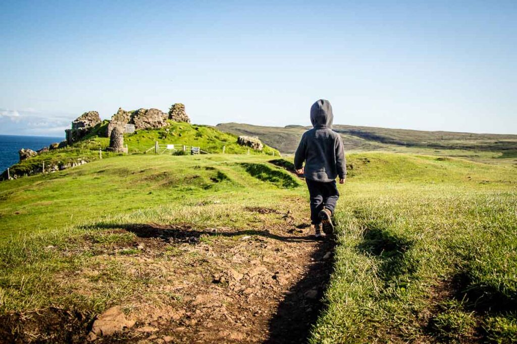 image of boy walking towards Duntulum Castle ruins on Isle of Skye