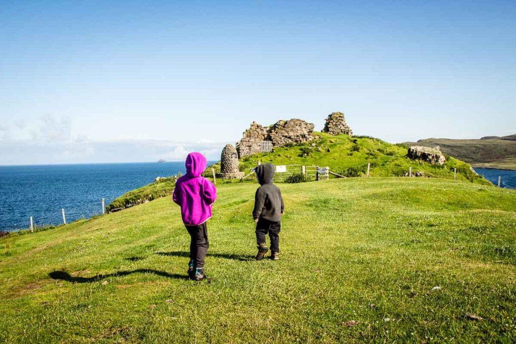 image of two kids walking towards Duntulum Castle Ruins on Isle of Skye