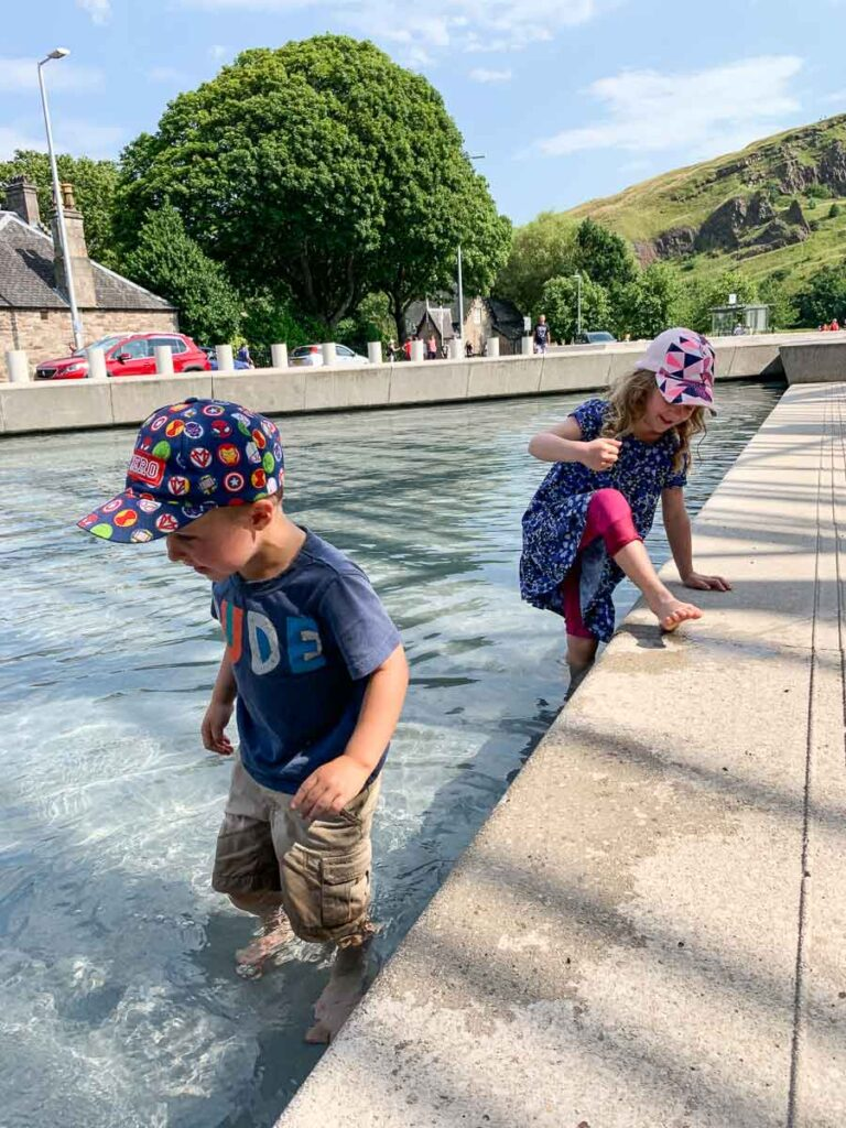 Image of two kids playing in wading pools in Edinburgh Scotland