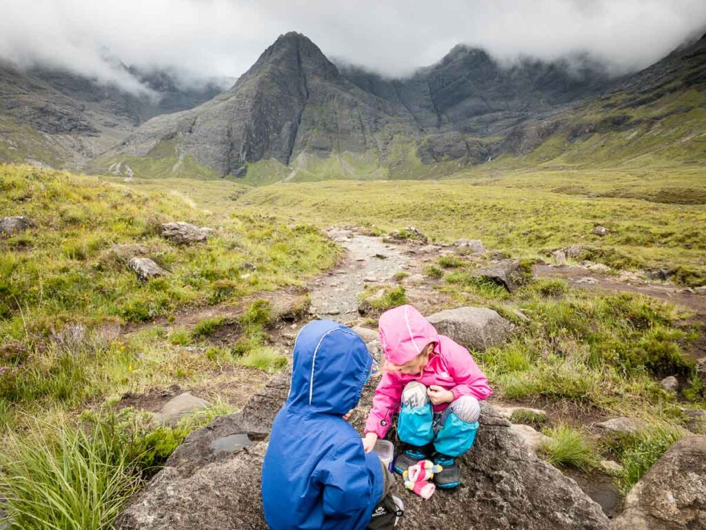 image of kids sitting on a rock eating with mountain in the background on Fairy Pools walk on Isle of skye