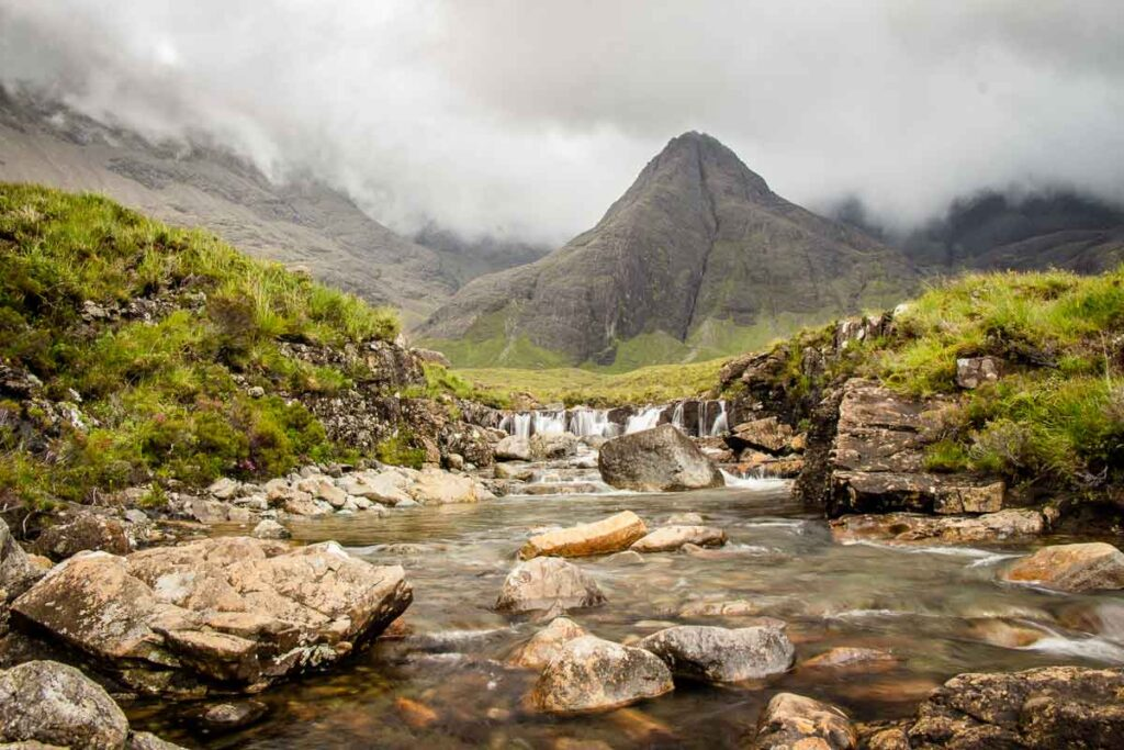 image of the Cuillin mountains and a waterfall and stream in front while hiking Fairy Pools on Isle of Skye