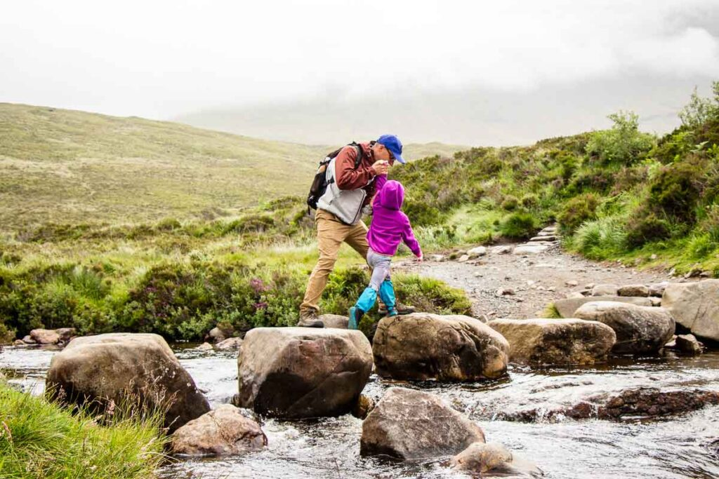 image of father and daughter jumping across rocks to cross a stream on the Fairy Pools Hike on Isle of Skye Scotland
