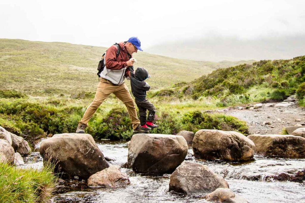 image of father and boy jumping across rocks crossing a stream on the Fairy Pools walk