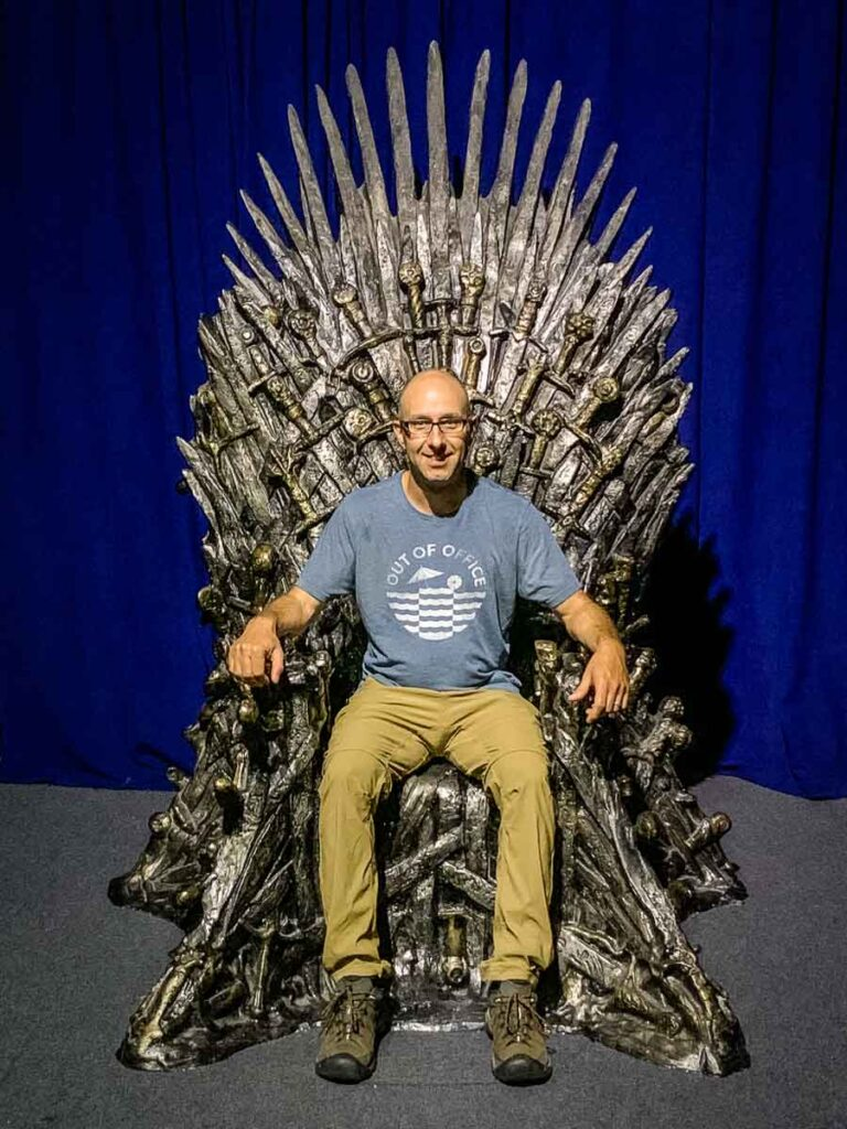 image of man sitting on replica of iron throne in Belfast Game of Thrones Exhibit