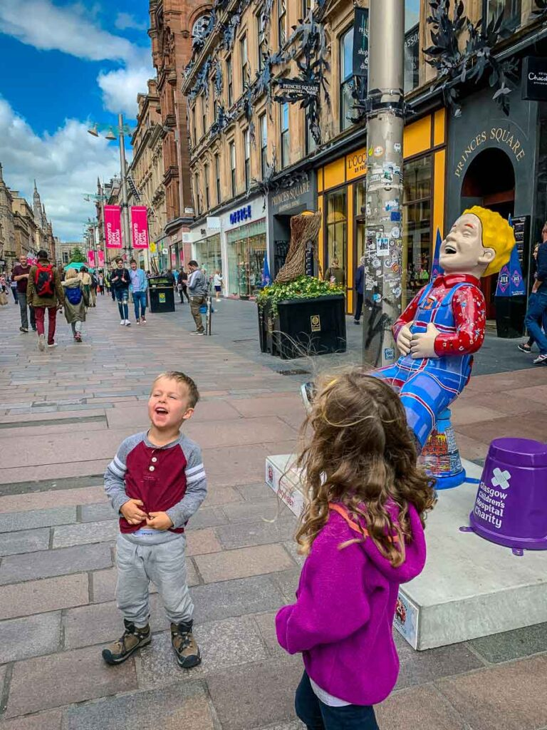 A boy imitates a street statue of Oor Wullie - part of the Oor Wullie's BIG Bucket Trail fundraiser for Scotland's children's hospital charities