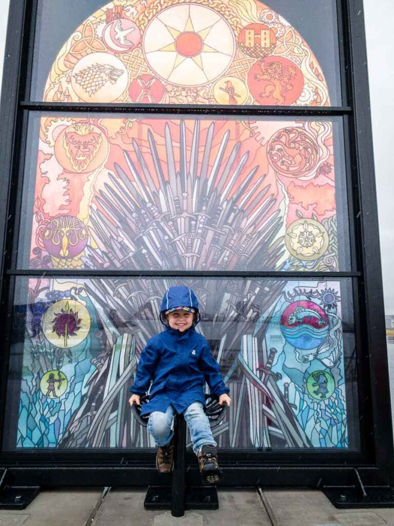 image of boy in blue rain jacket sitting in front of the Glass of Thrones exhibit in Belfast