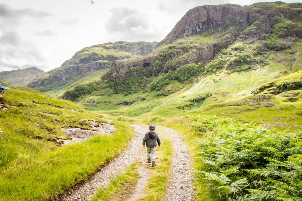 image of boy in grey hoodie walking on country road with mountains in the distance in Glencoe Scotland