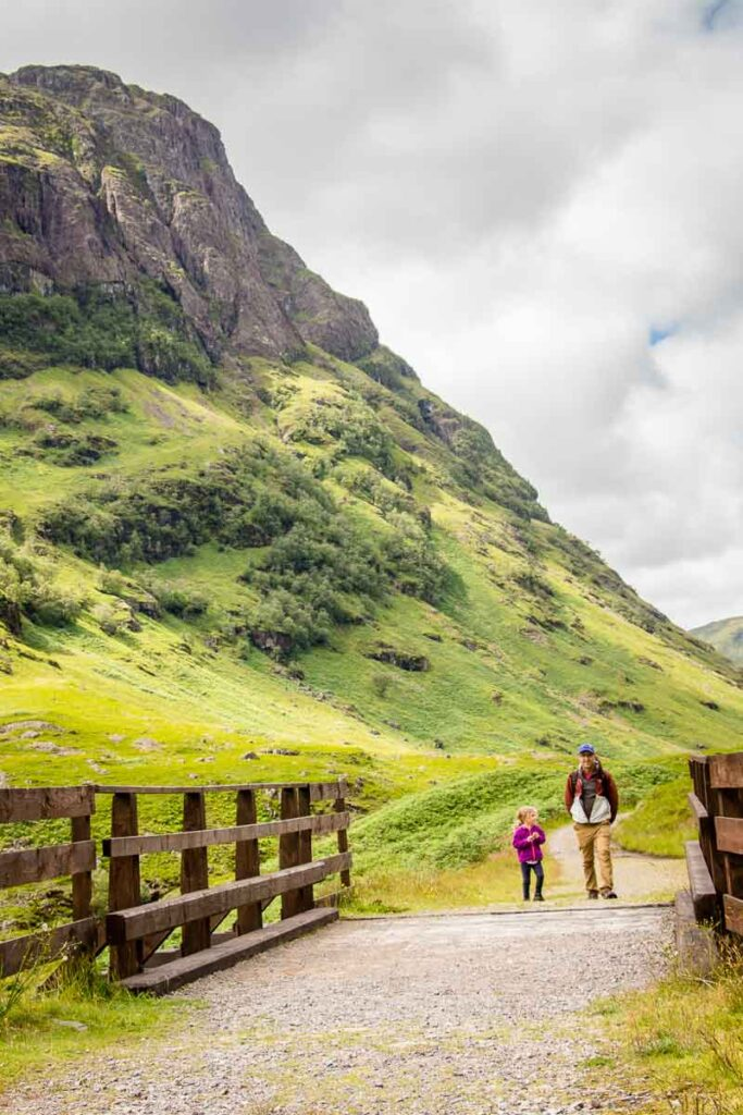 image of man and daughter crossing bride with mountains behind them in Glencoe Scotland