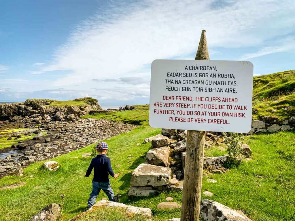 image of sign cautioning to stay away from cliffs ahead (found along Brother's Point hike on Isle of Skye Scotland)