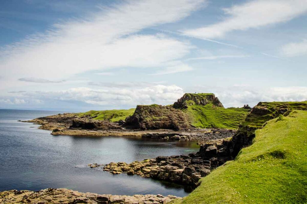 image of landscape on Brother's Point walk on Isle of Skye Scotland. Includes grass covered hills next to the ocean.