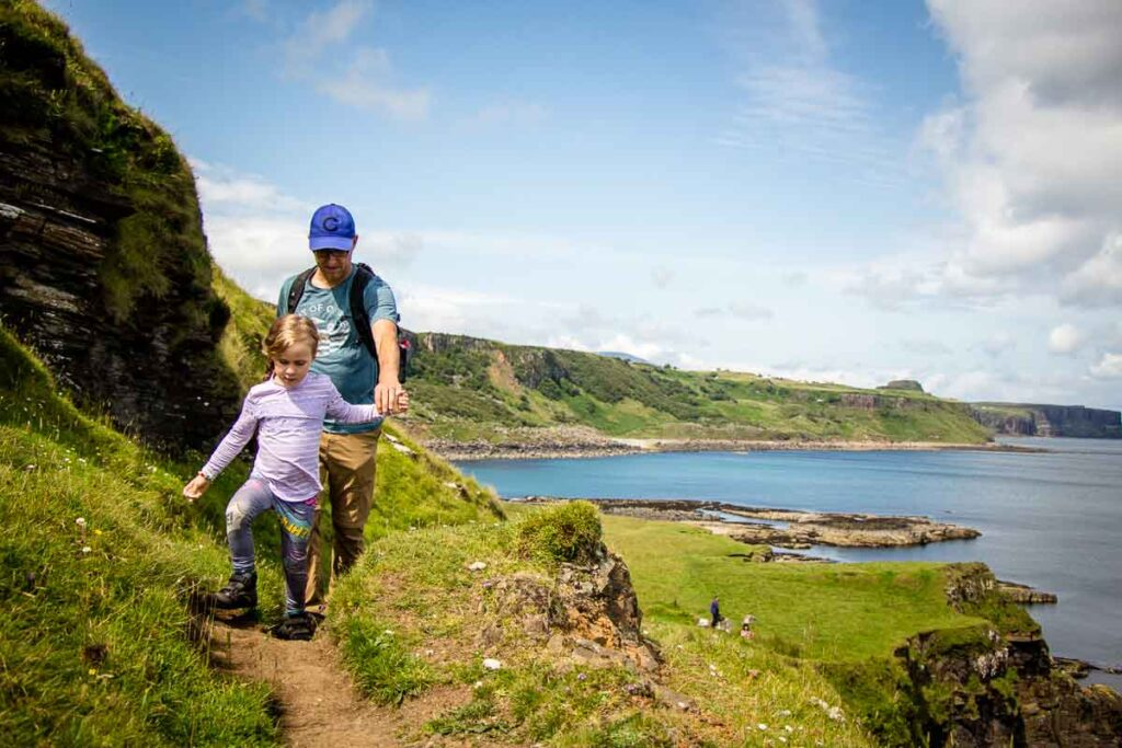 image of father holding daughters hand on Brother's Point hiking trail on Isle of Skye Scotland