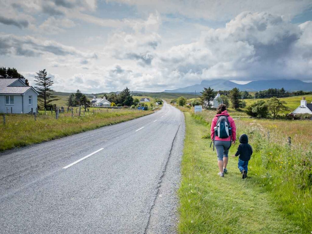 image of woman and boy walking alongside the road from carpark to Brother's Point hike on Isle of Skye Scotland