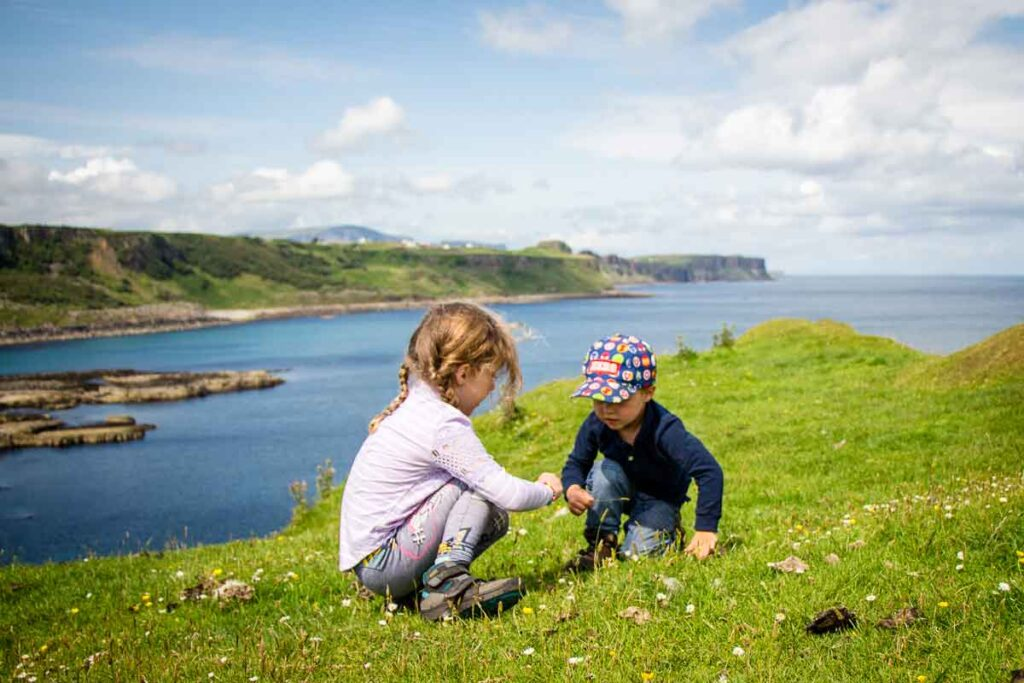 image of a boy and girl playing in the grass with the ocean and cliffs in the distance