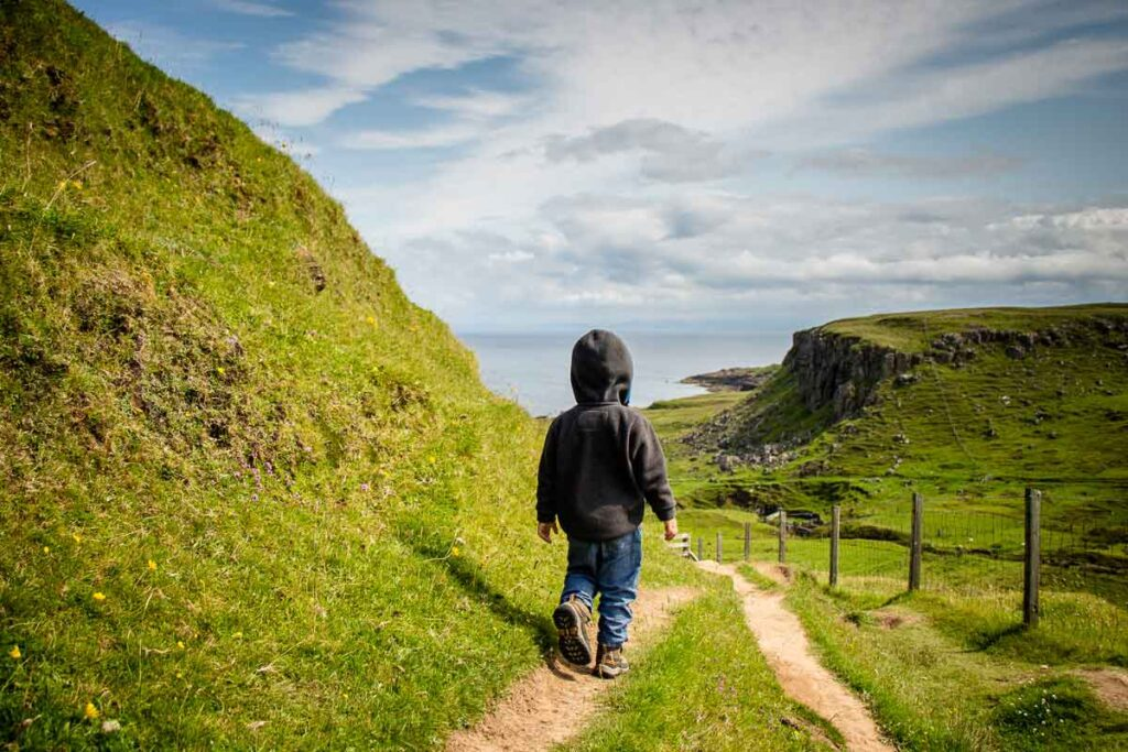 image of boy walking towards green hills and ocean in the distance on Brother's Point walk on Isle of Skye