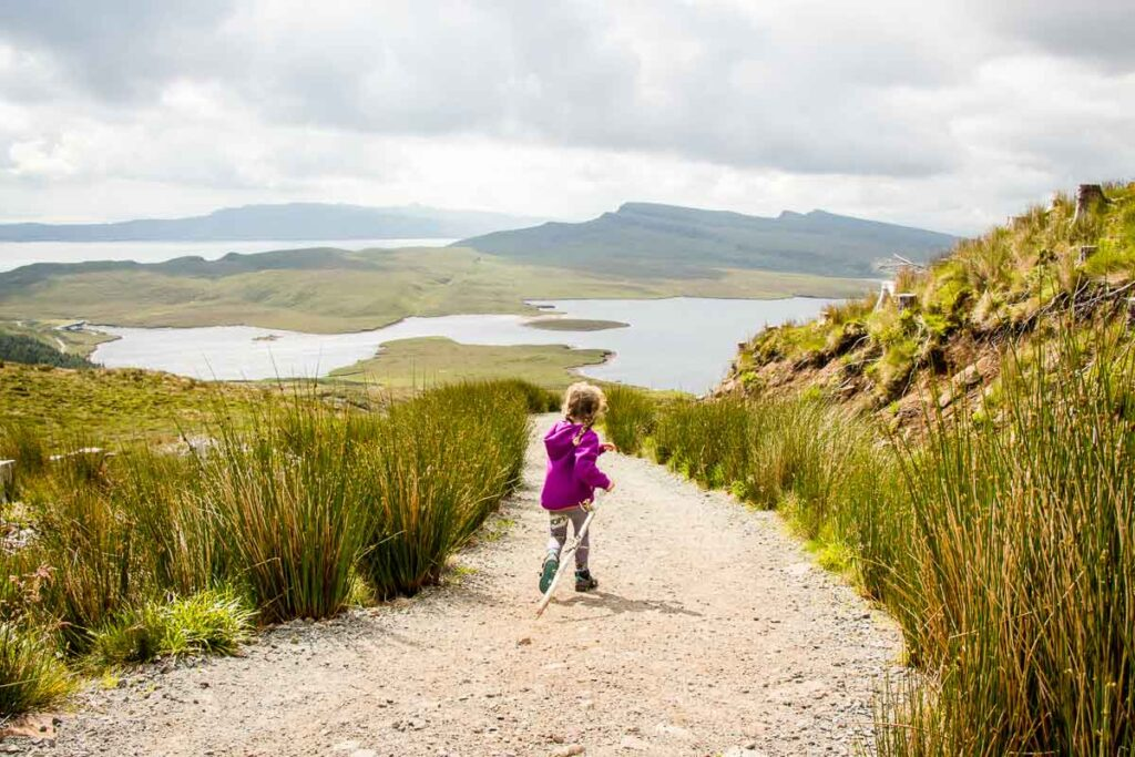 image of girl running on path with views of isle of skye in the distance