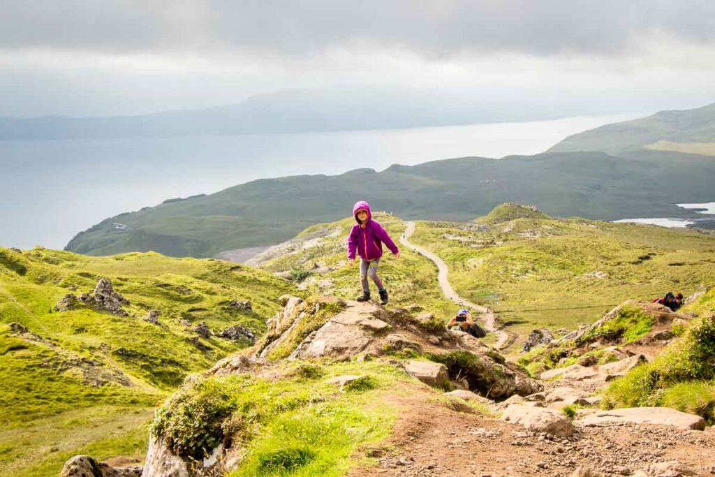 image of girl standing on rock with hiking trail behind her on the Old Man of Storr Walk on Isle of Skye Scotland