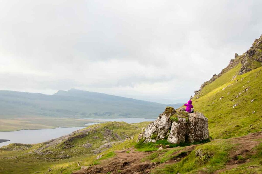 image of girl sitting on rock on the old man of storr hike on isle of skye scotland