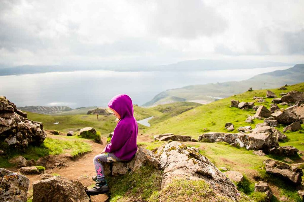 image of girl in purple hoodie sitting on rock with views of isle of skye scotland in the distance