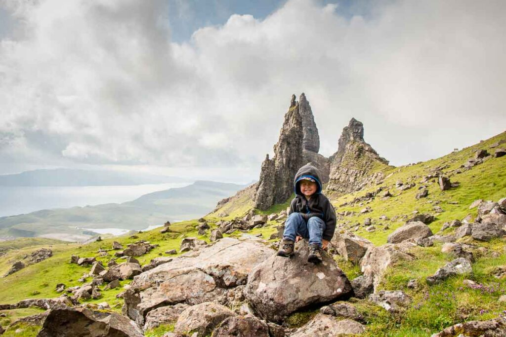 image of boy sitting on large rock with old man of storr in the background