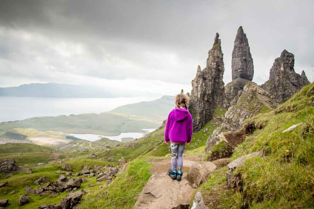 image of girl in purple hoodie looking over the Old Man of Storr rock pinnacles on one of the most popular isle of skye hikes