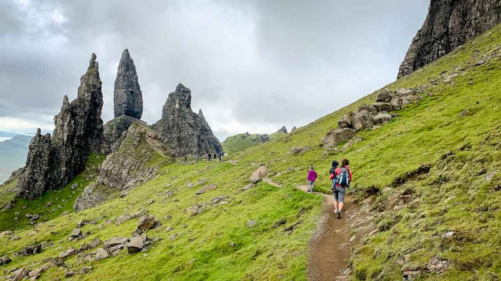 image of family hiking on trail with old man of storr in distance